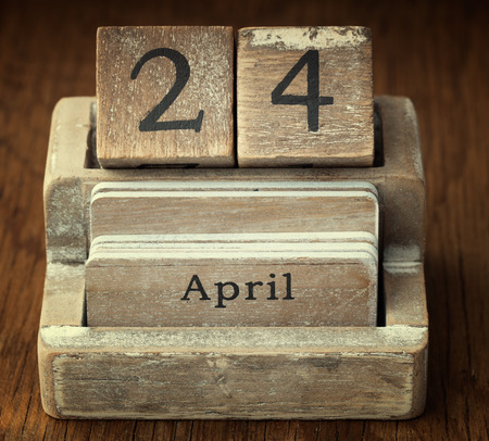 24 month old: A very old wooden vintage calendar showing the date 24th April on wood background Stock Photo