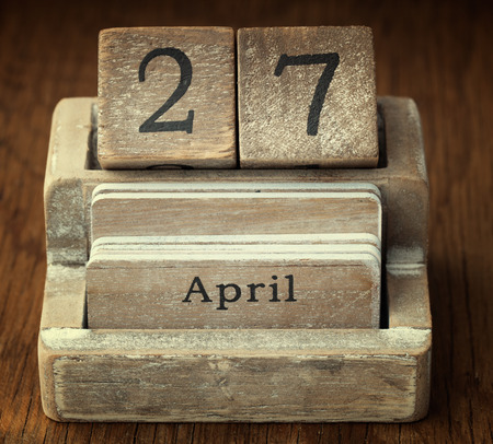27 years old: A very old wooden vintage calendar showing the date 27th April on wood background