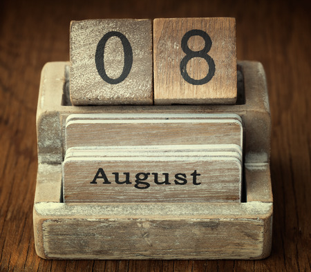 8 years old: A very old wooden vintage calendar showing the date 8th August on wood background Stock Photo