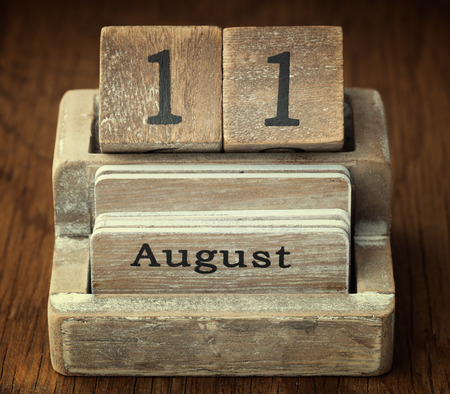 11 year old: A very old wooden vintage calendar showing the date 11th August on wood background