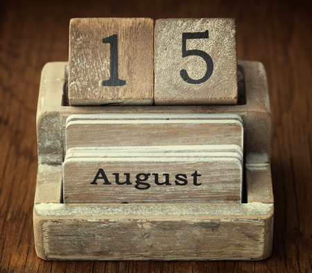 fifteen year old: A very old wooden vintage calendar showing the date 15th August on wood background Stock Photo