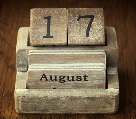 seventieth: A very old wooden vintage calendar showing the date 17th August on wood background Stock Photo