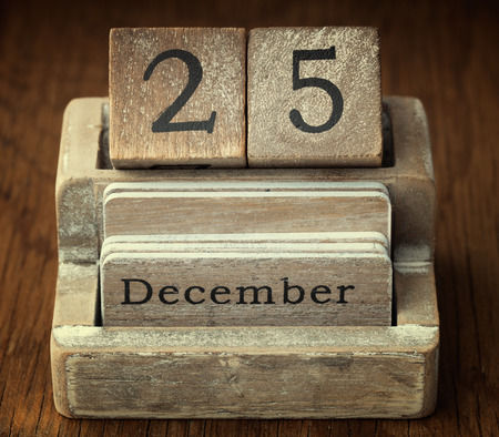 december 25th: A very old wooden vintage calendar showing the date of 25th December on wood background