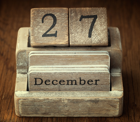 27 years old: A very old wooden vintage calendar showing the date of 27th December on wood background