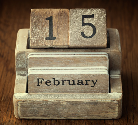 15 months old: A very old wooden vintage calendar showing the date 15th February on wood background Stock Photo