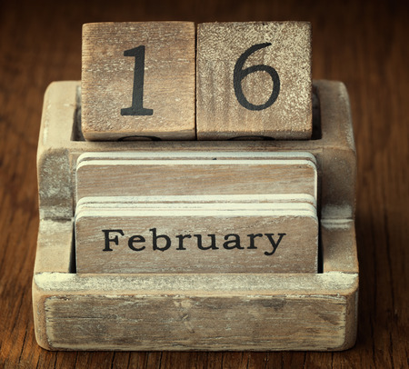 sixteen year old: A very old wooden vintage calendar showing the date 16th February on wood background