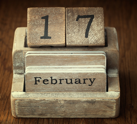 17 year old: A very old wooden vintage calendar showing the date 17th February on wood background