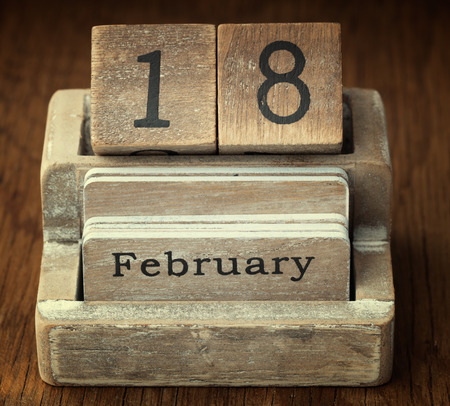 18 year old: A very old wooden vintage calendar showing the date 18th February on wood background