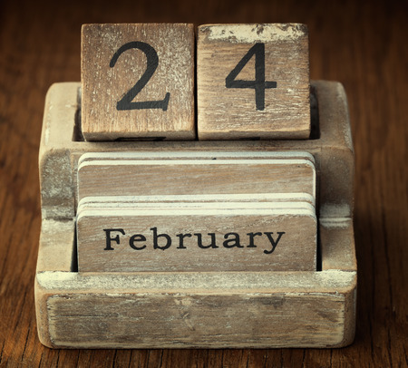 twenty four month old: A very old wooden vintage calendar showing the date 24th February on wood background
