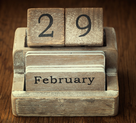 A very old wooden vintage calendar showing the date 29th February on wood background 스톡 콘텐츠