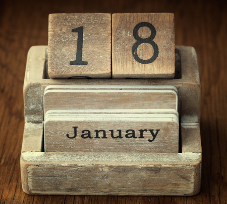 18 month old: A very old wooden vintage calendar showing the date 18th January on wood background