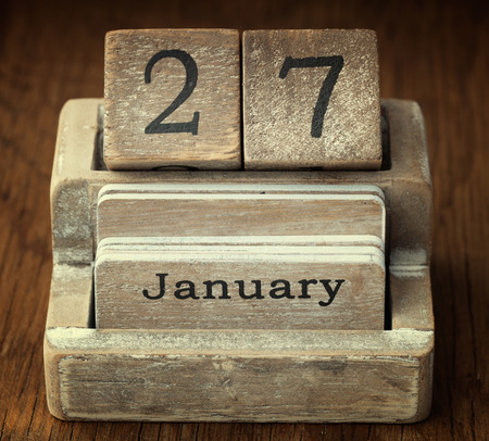 27 years old: A very old wooden vintage calendar showing the date 27th January on wood background