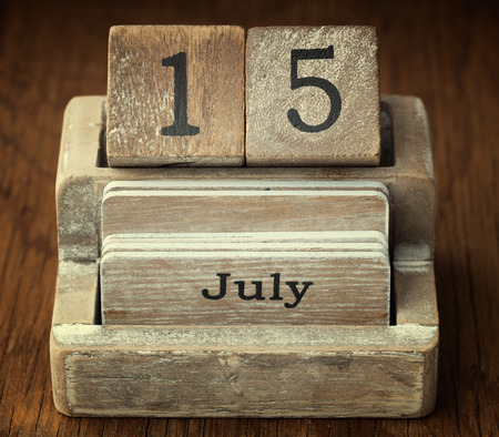 number 15: A very old wooden vintage calendar showing the date 15th July on wood background