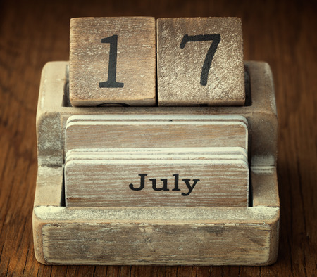 17 year old: A very old wooden vintage calendar showing the date 17th July on wood background Stock Photo