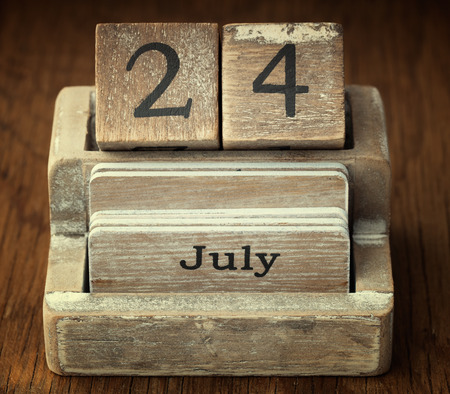 24 month old: A very old wooden vintage calendar showing the date 24th July on wood background
