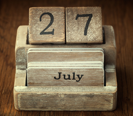 27 years old: A very old wooden vintage calendar showing the date 27th July on wood background Stock Photo