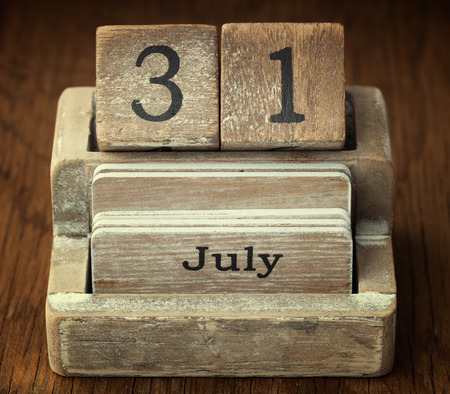 A very old wooden vintage calendar showing the date 31st July on wood background