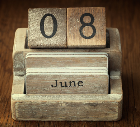 A very old wooden vintage calendar showing the date 8th June on wood background photo