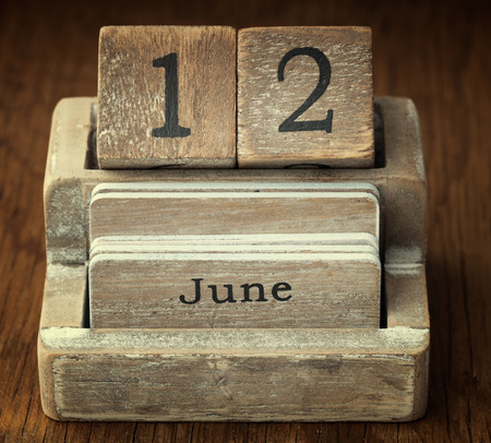twelve month old: A very old wooden vintage calendar showing the date 12th June on wood background