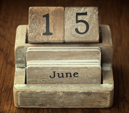 15 months old: A very old wooden vintage calendar showing the date 15th June on wood background Stock Photo