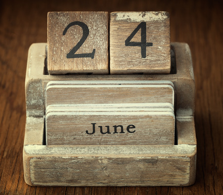 24 month old: A very old wooden vintage calendar showing the date 24th June on wood background Stock Photo