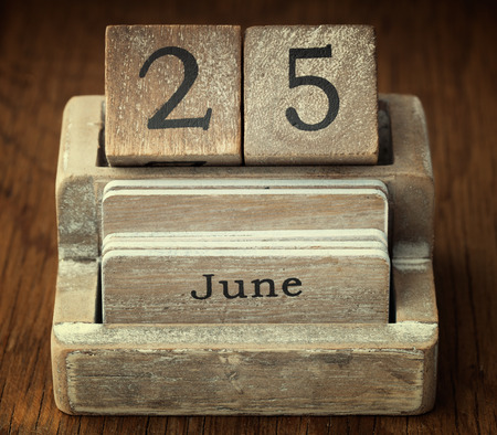 25 years old: A very old wooden vintage calendar showing the date 25th June on wood background