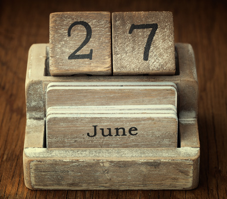 27 years old: A very old wooden vintage calendar showing the date 27th June on wood background