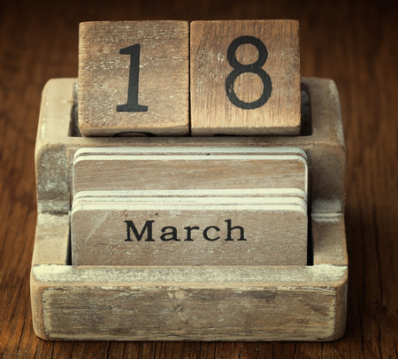 18 year old: A very old wooden vintage calendar showing the date 18th March on wood background