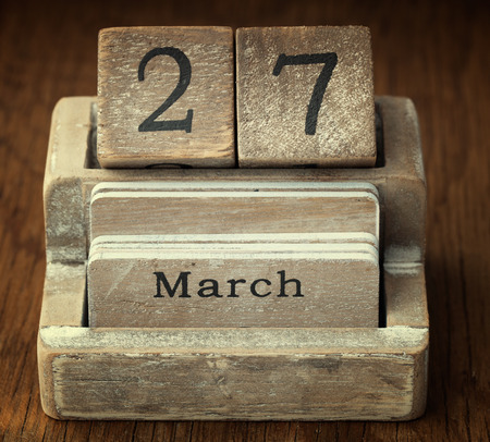 27 years old: A very old wooden vintage calendar showing the date 27th March on wood background