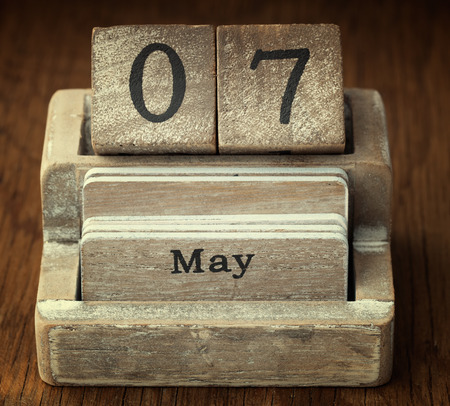 seventh: A very old wooden vintage calendar showing the date 7th May on wood background
