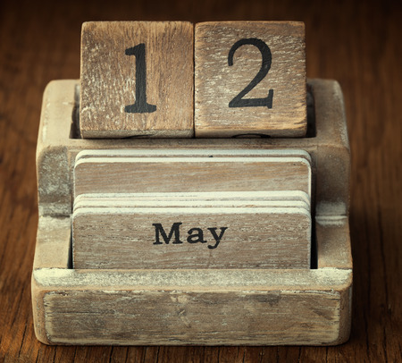 twelve month old: A very old wooden vintage calendar showing the date 12th May on wood background