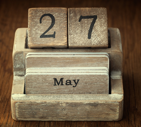 27 years old: A very old wooden vintage calendar showing the date 27th May on wood background Stock Photo