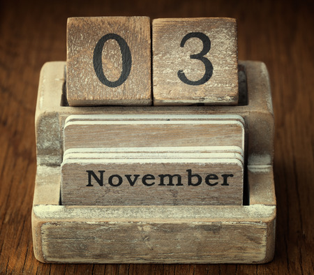 three months old: A very old wooden vintage calendar showing the date of 3rd November on wood background