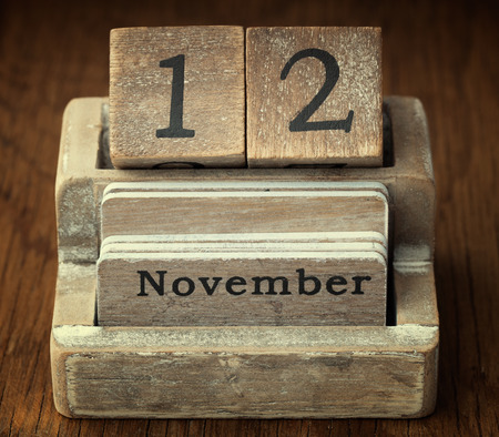 A very old wooden vintage calendar showing the date of 12th November on wood background