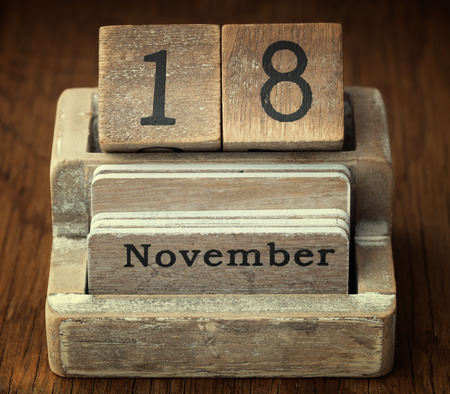 18 month old: A very old wooden vintage calendar showing the date of 18th November on wood background
