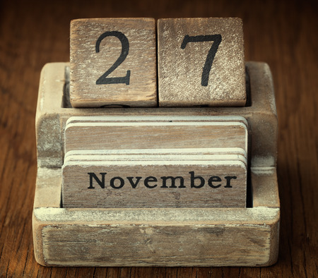 27 years old: A very old wooden vintage calendar showing the date of 27th November on wood background