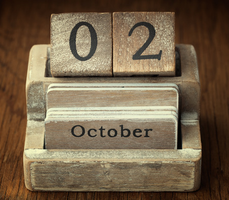 A very old wooden vintage calendar showing the date of 2nd October on wood background photo