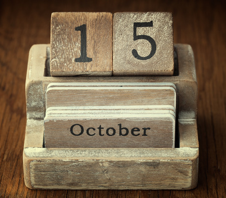 15 months old: A very old wooden vintage calendar showing the date of 15th October on wood background