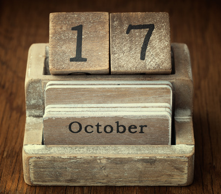 17 year old: A very old wooden vintage calendar showing the date of 17th October on wood background