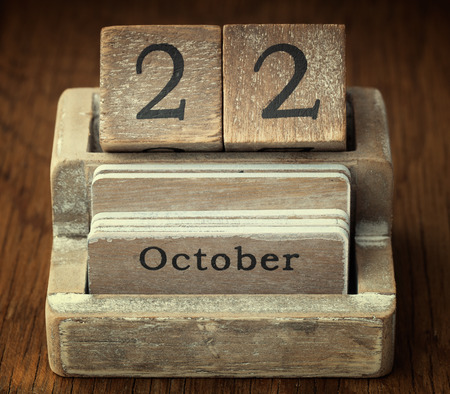 A very old wooden vintage calendar showing the date of 22nd October on wood background photo