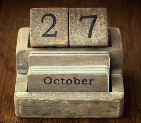 27 years old: A very old wooden vintage calendar showing the date of 27th October on wood background