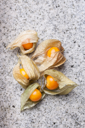calyx: An calyx open, exposing the ripe fruit of physalis peruviana on a white slate of marble