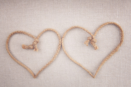string together: Two love hearts made of string crossed together on fabric vintage background Stock Photo