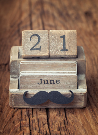 padres: Calendario viejo vintage que muestra la fecha de 21 de junio, que es la fecha del d�a de padres con el bigote de madera Foto de archivo