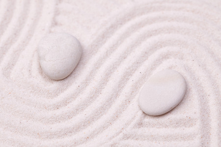 Zen garden with white marble rocks and wave pattern in the white sand Stock Photo