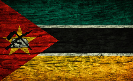 antique rifle: The national vintage flag of Mozambique on wooden surface