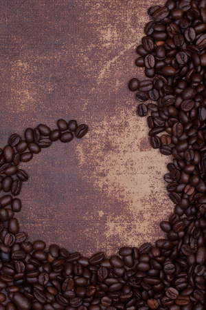 faux: Dark roasted coffee beans on an old faux leather material background
