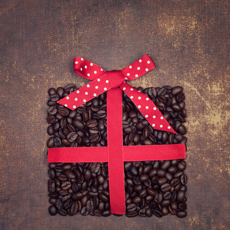 faux: The shape of a  present made out of roasted coffee beans  with polka dot ribbon on a faux leather material background