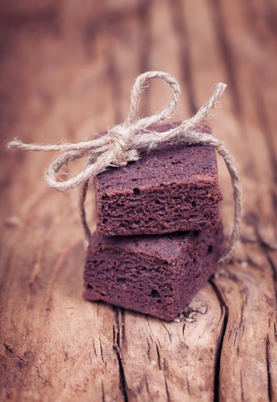 sting: Chocolate mini brownie bites tied up with a sting ribbon on an old rough wooden surface