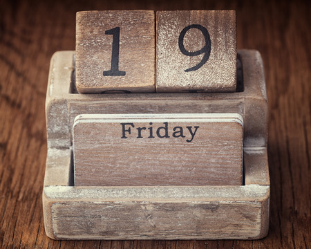 19 years old: Grunge calendar showing Friday the nineteenth on wood background Stock Photo